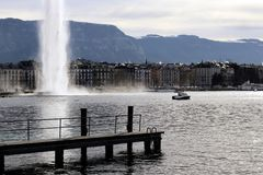 Geneva cityscape pier and Water jet dEau Water Fountain and facades in winter. Geneva cityscape with wharf pier landing stage, the low part of the famous Geneva stock photo