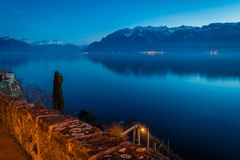 Geneva lake at night with snowy mountains. In the background Royalty Free Stock Images
