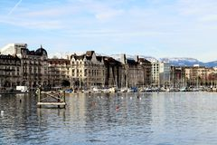 Geneva lakefront buildings. The rows of buildings along lake Geneva, with boats, from the swiss beach of Bains des Paquis in winter, Genève canton in stock image