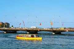 Excursion ferry in Geneva Lake and Bergues bridge with flags. Geneva, Switzerland - August 30, 2016: Excursion ferry in Geneva Lake and Pont des Bergues bridge stock image