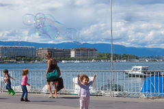 Geneva, Switzerland - June 17, 2016: The children and with soap bubbles attraction at Lake promenade. In the old town of Geneva, Switzerland on 28 July, 2010 stock image