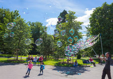 Geneva, Switzerland - June 17, 2016: The children and with soap bubbles attraction at park. In the old town of Geneva, Switzerland on 28 July, 2010. It is the stock images