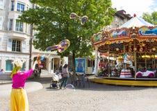 Genewa Szwajcaria, Czerwiec, - 17, 2016: Dzieci z mydlanych bąbli przyciąganiem blisko miasta carousel i Zdjęcia Royalty Free