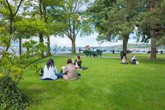 Genf, die Schweiz - 17. Juni 2016: Die Leute, welche auf dem Gras in einem Park die Ufergegend sitzen Stockfotos