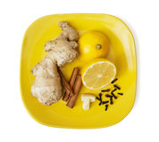 Gengibre, canela, limão, alho e cravos-da-índia na placa amarela Fotos de Stock
