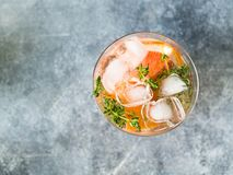 Genièvre alcoolique de cocktail amer, thym et pamplemousse en verre Limonade de fruit Fond gris Vue supérieure Copiez l'espace photo stock