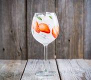 Genièvre avec la fraise et la glace en verre de vin image libre de droits