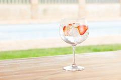 Genièvre de fraise et cocktail de tonique par une piscine dehors photo stock