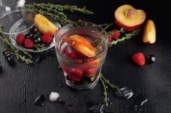 Genièvre de thym de framboise et cocktail de tonique avec le cassis et les pêches photo stock