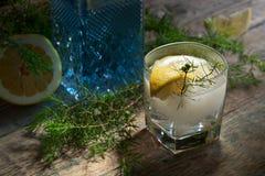 Genièvre, tonique et citron bleus sur une vieille table en bois photographie stock