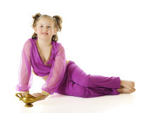 Geni with Her Lamp. A young elemantary genie relaxed by her golden lamp.  On a white background Stock Photo
