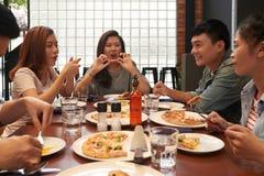 Genießen der Pizza und der guten Firma stockfoto