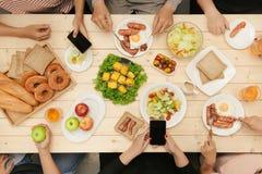 Genießen des Abendessens mit Freunden Draufsicht der Gruppe von Personen, die zusammen beim Sitzen am Holztisch zu Abend isst lizenzfreies stockbild