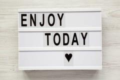 ` Genießen heute ` Wort auf lightbox über weißem hölzernem Hintergrund, für stockbilder
