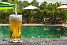 Genießen Sie Bier neben Swimmingpool Lizenzfreie Stockfotografie
