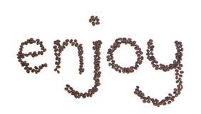 Genießen Sie buchstabiert mit den Kaffeebohnen, die auf Weiß getrennt werden Stockbild
