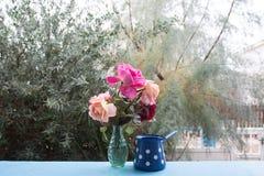Genießen Sie einige Freizeit auf der Terrasse mit Rosenblumenstrauß lizenzfreie stockfotos