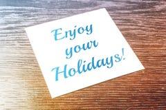 Genießen Sie Ihre Feiertags-Anzeige auf dem Papier, das auf Holztisch liegt stockbilder