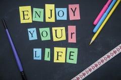 Genießen Sie Ihre Lebenaufschrift auf einer Tafel Stockbilder