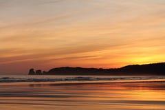 Genießen von Ansicht kurz vor Sonnenaufgang von Schattenbild deux jumeaux im bunten Sommerhimmel auf einem sandigen Strand Stockfoto
