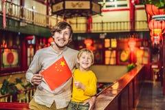 Genießen von Ferien in China Glückliche Touristen Vati und Sohn mit einer chinesischen Flagge auf einem chinesischen Hintergrund  stockbilder