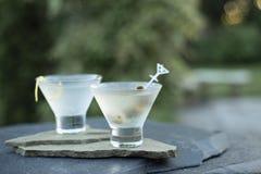 Genießen von frisch gerüttelten schmutzigen Gin- und Wodkamartinis an einem warmen Sommerabend mit Freunden und Familie während e stockfotos