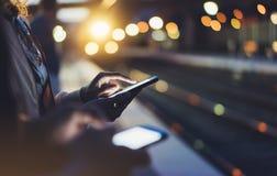 Genießen von Reise Junge Frau, die auf Stationsplattform auf elektrischem beweglichem Zug des Hintergrundlichtes unter Verwendung lizenzfreie stockfotos