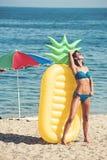 Genießen von Sonnenbräune Schöne junge Frau an einem Pool Dünne junge Frau im Bikini auf der gelben Luftmatraze stockfoto