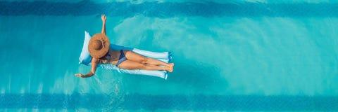 Genießen von Sonnenbräune Schöne junge Frau an einem Pool Draufsicht der dünnen jungen Frau im Bikini auf der blauen Luftmatraze  lizenzfreie stockfotos