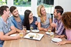 Genießende Freunde beim Essen von Sushi und von Wein Stockbild