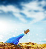 Genie. Blue glass bottle in sand and airy clouds like genie stock photos