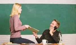 Genie?en des Studentenlebens Hochschul- oder Studenten Ordnende Papiere des h?bschen Lehrers und des h?bschen Schulleiters paare stockbild