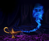 Genie-lamp. Maagic Aladdin genie lamp with genie arising from blue smoke Stock Images