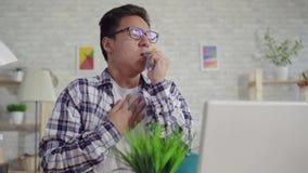 Geniet de portret jonge Aziatische mens in een astmatisch overhemd van de nevel van het hoesten zitting bij laptop stock video