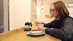 Geniet het heerful meisje Ð ¡ van een hete drank met dessertzitting in de avond in een koffie Aantrekkelijke Kaukasische vrouw in stock video