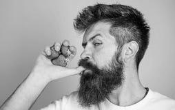Geniet het mensen strikte gezicht van vers drinkt aardbeisap vers sapconcept De mens drinkt aardbeisap zuigt duim als drank stock fotografie