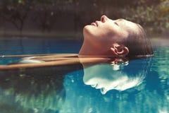 Geniet van de zomer Vrouw het ontspannen in het poolwater Royalty-vrije Stock Fotografie