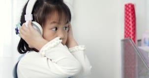 Geniet van elke dag Sluit omhoog een aardig klein Aziatisch meisje die aan muziek omhoog luisteren terwijl hand stock footage