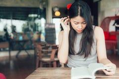 Geniet van ontspannen tijden met de Aziatische vrouwen van lezingsboeken de mooie Thaise tiener een boek las stock fotografie