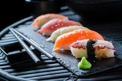Geniet van uw die Nigiri-sushi van verse zeevruchten worden gemaakt Stock Fotografie