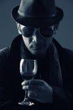 Genio criminal y un vidrio de vino Fotografía de archivo libre de regalías