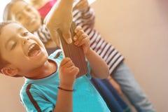 Genitore di grido di attimo del ragazzino che prova a portare via telefono cellulare con i bambini che ridono da dietro a casa fotografie stock