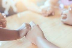 Genitore e bambini che si tengono per mano insieme e che pregano immagini stock