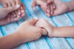 Genitore e bambini che si tengono per mano insieme e che pregano fotografia stock