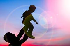 Genitore felice con i bambini che giocano sulla siluetta di estate della natura immagine stock libera da diritti