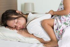 Genitore stanco che prova a prendere per dormire con il suo bambino che la importuna immagini stock
