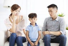 Genitore turbato e ragazzino che si siedono sul sofà fotografia stock