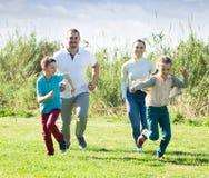 Genitori allegri con i bambini all'aperto Immagine Stock