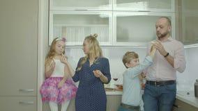 Genitori allegri con i fratelli germani che dividono frutti in cucina video d archivio