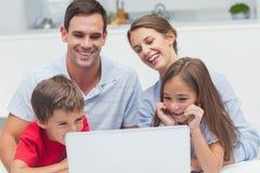 Genitori allegri e bambini che per mezzo di un computer portatile Fotografie Stock
